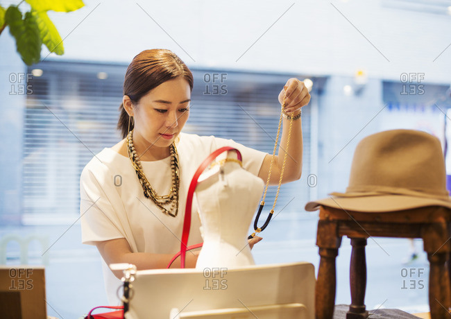 Woman working in a fashion boutique in Tokyo, Japan, holding jewellery.