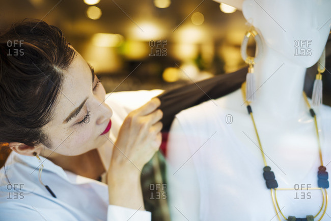 Woman working in a fashion boutique in Tokyo, Japan, dressing a mannequin.