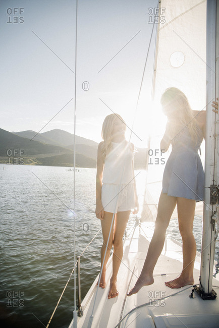 Portrait of two blond sisters on a sail boat.