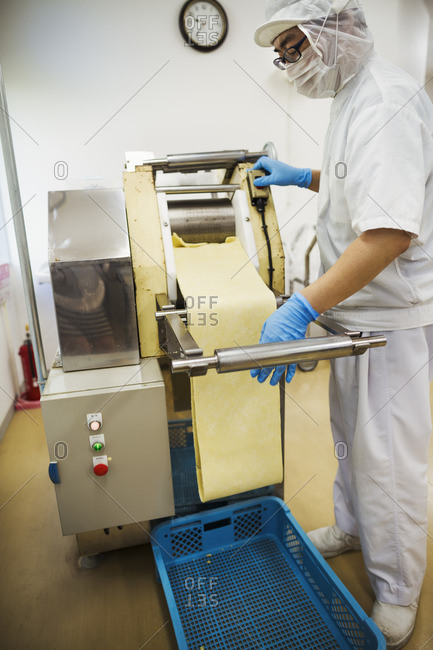 Worker in a factory producing Soba noodles, rolling out the noodle dough into thin sheets.