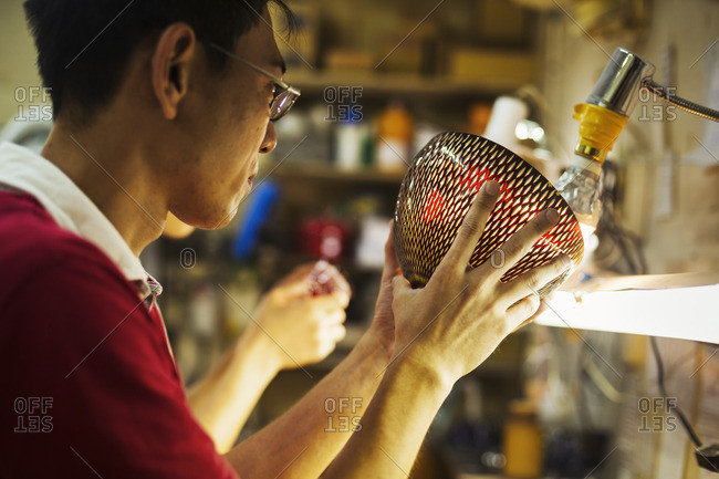 A craftsman in a glass maker's workshop holding a vase with a delicate geometric pattern up against a light.