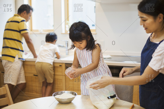Family home. Two parents and two children preparing a meal.