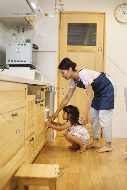 Family home. A woman and a girl bending down to look in an oven.