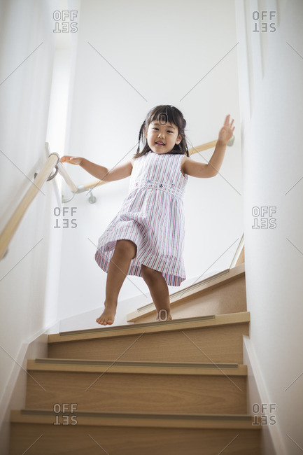 Family home. A young girl walking down stairs.