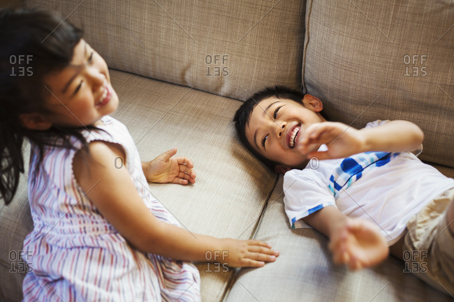 Family home. Two children playing on the floor, giggling.