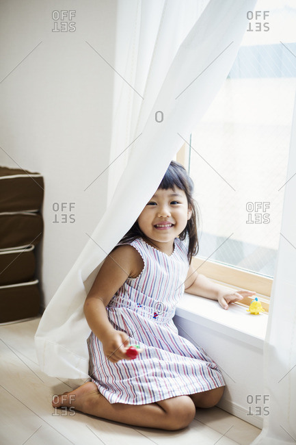 Family home. A girl playing by a window, hiding behind the net curtain.