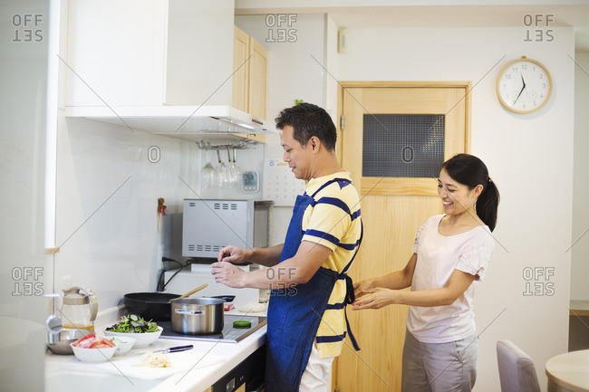 Family home. A man and woman, a wife tying her husband's apron in their kitchen.