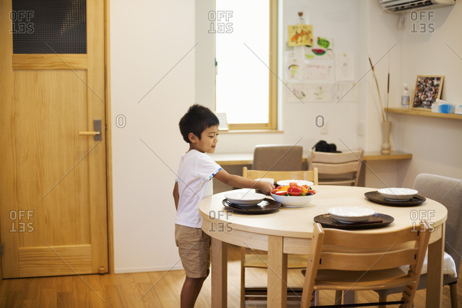 Family home. A boy setting the table for a meal.