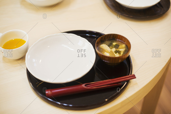 Family home. A table place set for a meal. Mat, bowl and chopsticks.