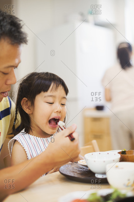 Family home. A man feeding his daughter at a meal.