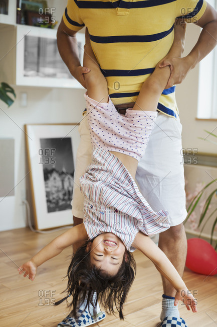 Family home. A man playing with his daughter, holding her upside down.