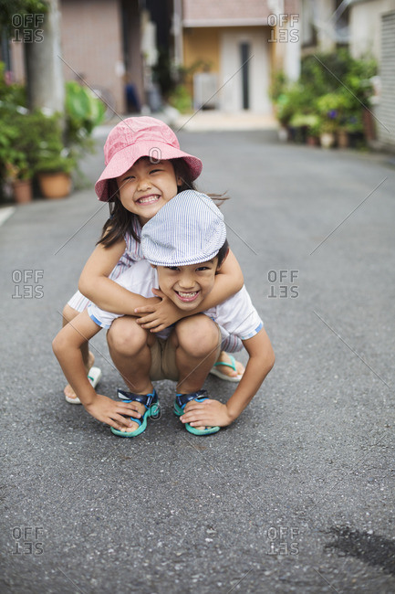 Family home. Two children, a boy and girl playing outdoors.