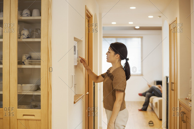 Family home. A woman adjusting the thermostat on a wall in the house.
