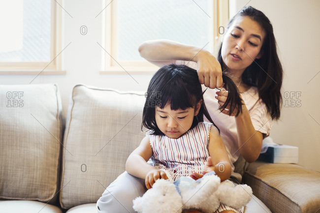 Family home. A mother combing her daughter's hair.