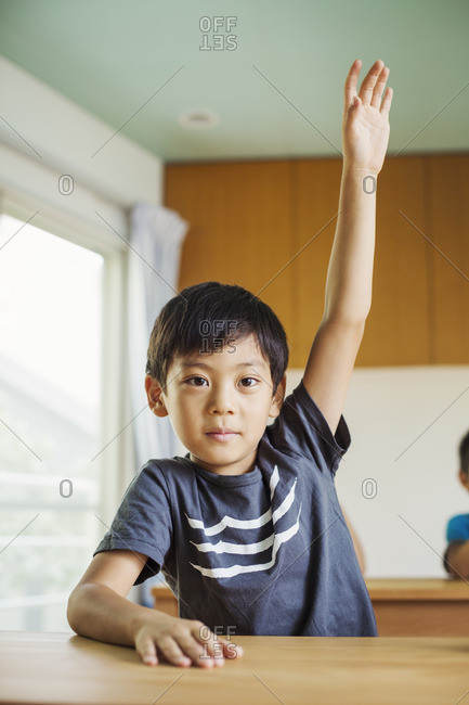 A boy with his hand up ready to answer a question.