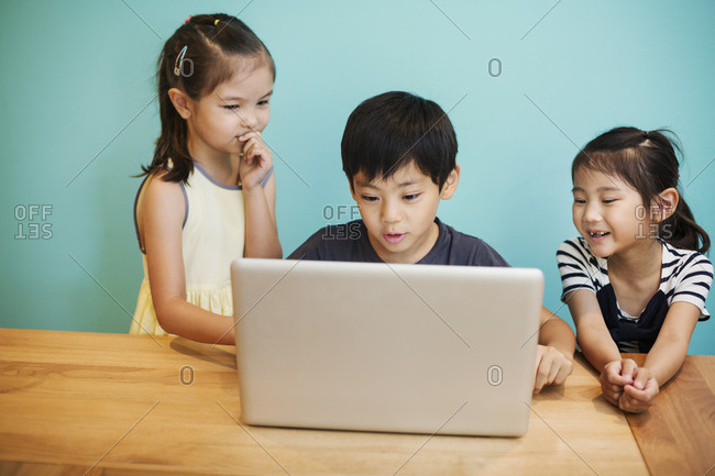A group of children in school, three children sharing a laptop computer.
