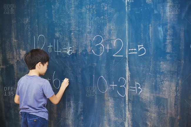 A group of children in school. A boy writing in chalk on a chalkboard.
