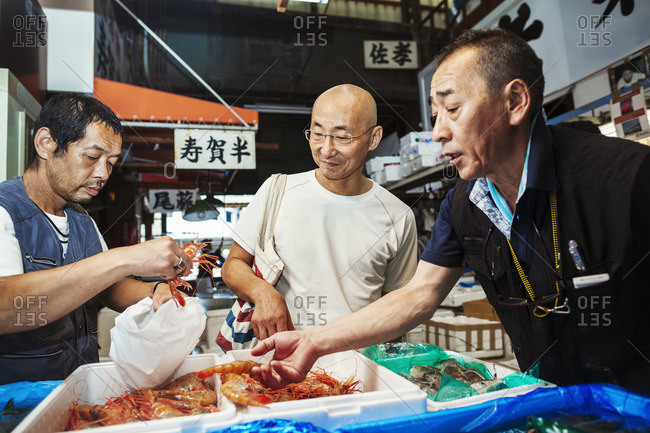 Japan - August 12, 2016: A traditional fresh fish market in Tokyo. Two people selecting shellfish for a customer to buy, filling a bag from boxes of prawns.
