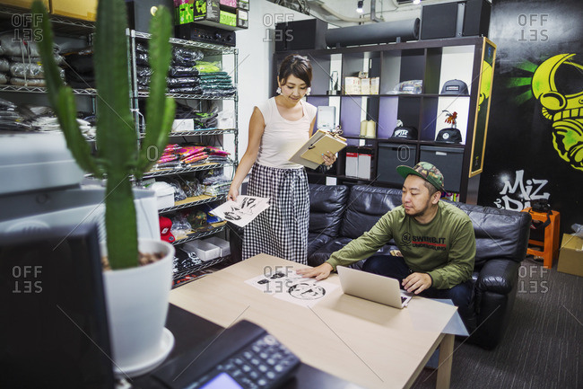 Japan - August 23, 2016: Design Studio. Two people in an office stockroom, looking at designs. Stock of clothes and hats on the shelves.