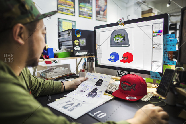Japan - August 23, 2016: A man, a designer working on screen creating designs for baseball caps.
