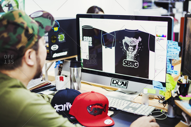 Japan - August 23, 2016: Design Studio. A man seated at a desk using a computer to design tee shirt prints.