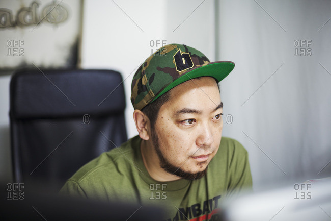Japan - August 23, 2016: Design Studio. A man wearing a baseball cap looking at a screen.