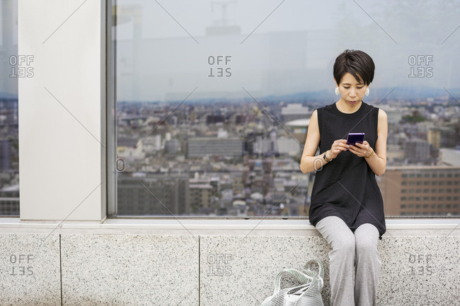 A woman seated by a window with a view over a large city with her back to the view, using her smart phone.