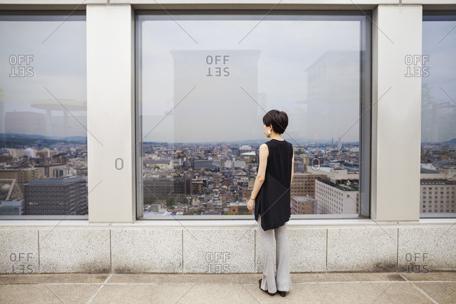 A woman standing looking over a city from a high viewing point.