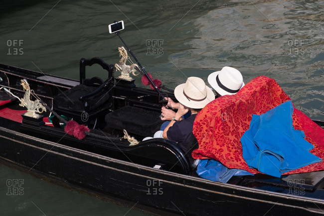 Two tourists in matching hats filming themselves on a gondola in Venice