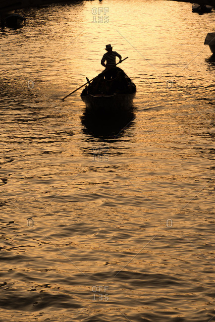 Silhouette of a gondola on a canal in Venice at sunset