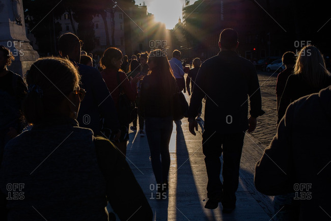 Rome, Italy  - October 7, 2016: Strongly backlit shot of people walking towards a setting sun with the people in silhouette