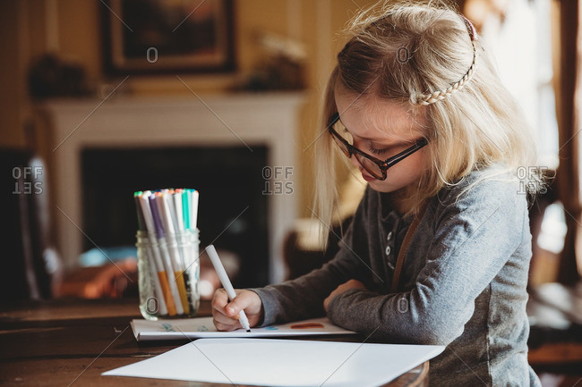 Girl wearing glasses writing with a marker pen