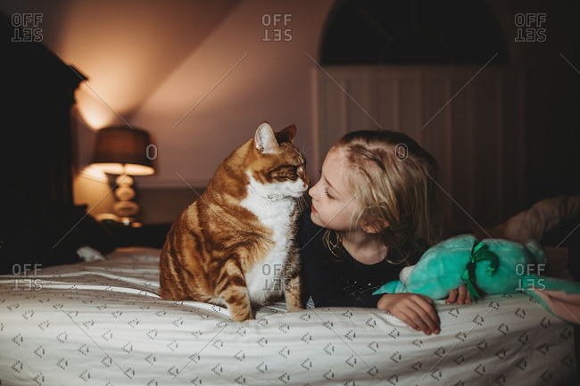 Girl lying on her bed nuzzling her pet cat