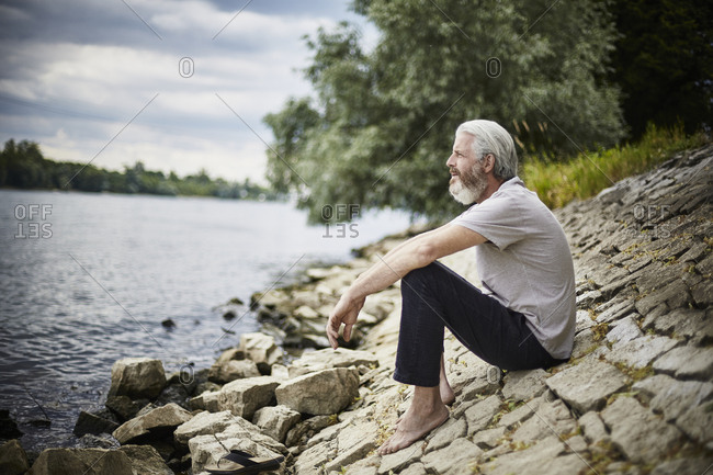 Bearded mature man sitting at the riverside