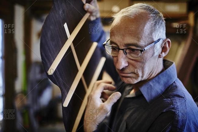 Guitar maker listening to sound of guitar body