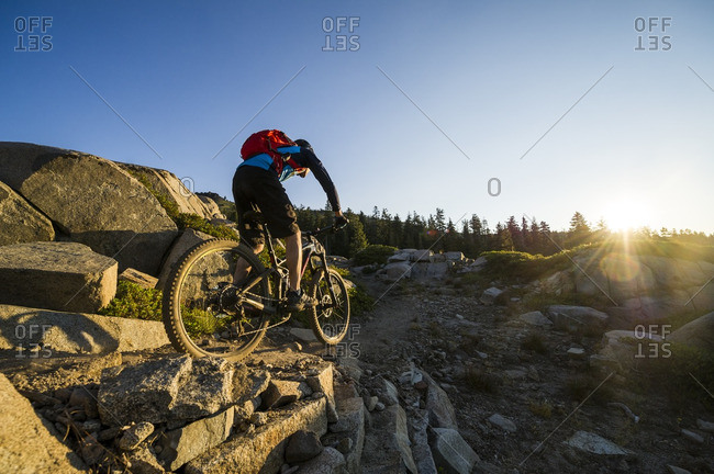 A man rides his mountain bike along the Donner Lake Rim Trail at sunrise near Truckee, California.
