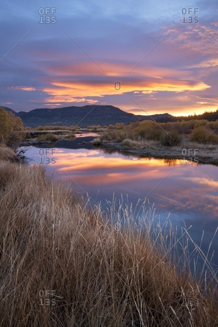 A beautiful sunrise reflects in the West Fork Carson River in the fall in Hope Valley, California.