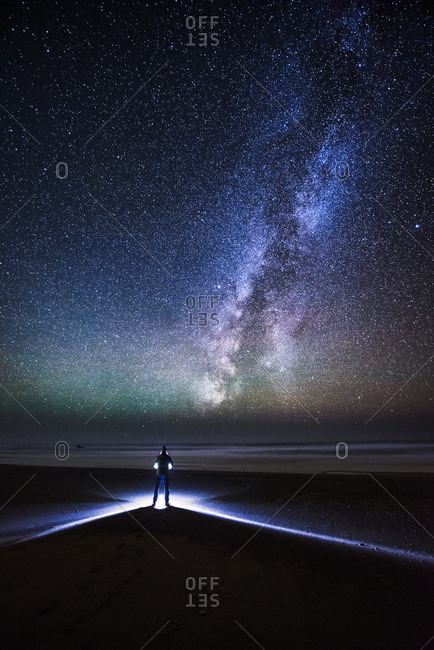 A man stands on Westport Beach on a perfectly clear night looking out over the Pacific Ocean, the Milky Way and stars above.  Westport is just north of Fort Bragg and just south of the Lost Coast.