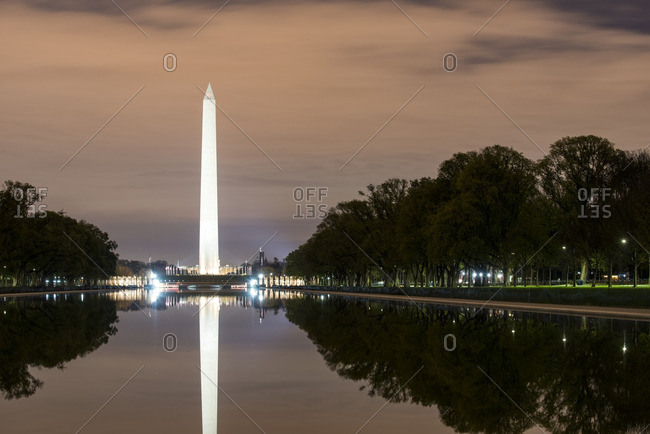 The Lincoln Memorial Reflecting Pool reflects the Washington Monument at night in the National Mall of Washington DC, USA.
