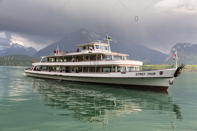 Oberhofen - March 4, 2016: Excursion ship Stadt Thun on Lake Thun with an approaching thunderstorm, spring, Oberhofen, canton Berne, Switzerland, Alps