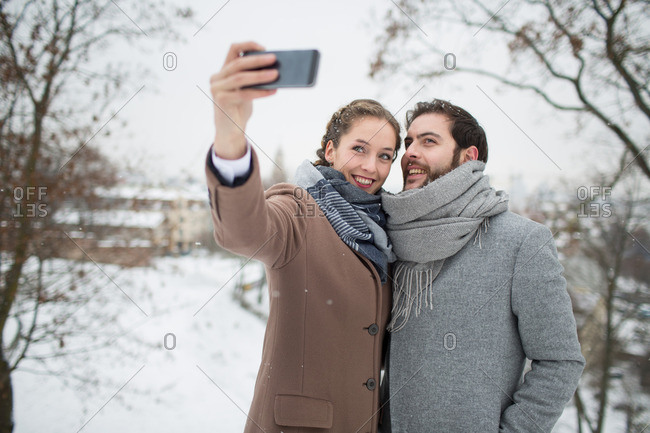 Young beautiful couple smiling and making selfie on blurred snowy landscape