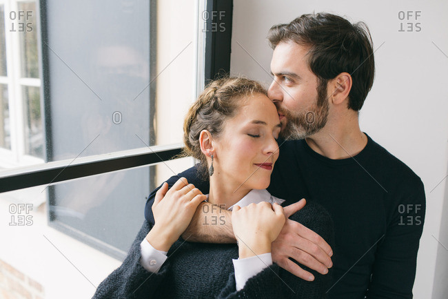 Young beautiful couple embracing while sitting on window sill