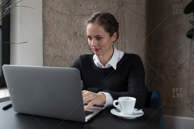 Young pretty woman sitting in office and working on computer