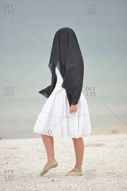 Female in white dress with black shawl covering her head and face standing outdoors