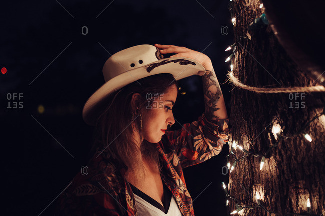 Side view of tattooed stylish woman in cowboy hat standing near tree decorated with burning garland