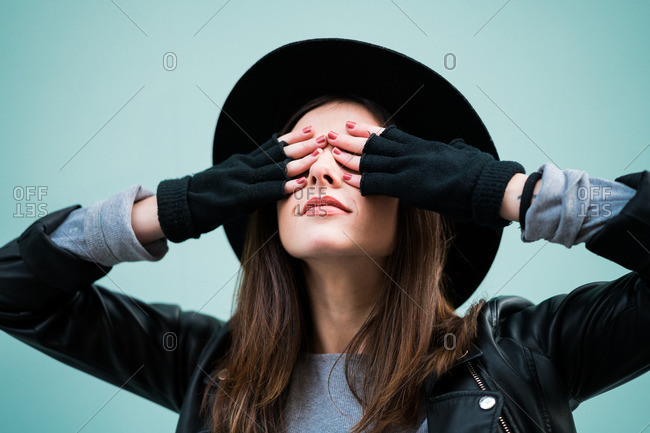 Young woman posing with eyes closed with hands Horizontal studio shot