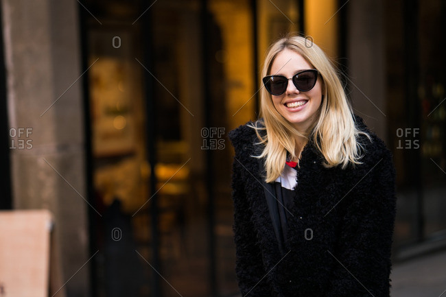 Smiling young lady wearing sunglasses smiling and walking in the street