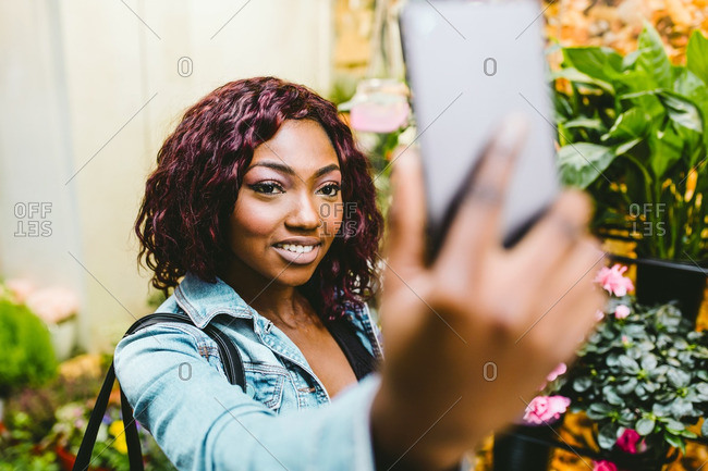 Portrait of pretty young woman using her mobile phone in the street