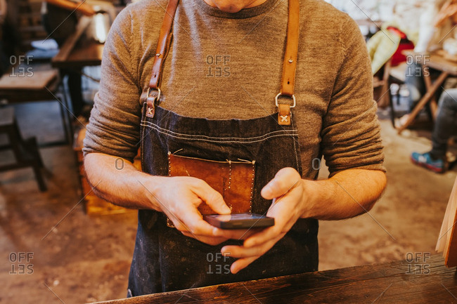 Man dressed in jeans apron with patch browsing phone