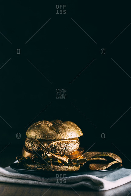 Gourmet golden burger on dark background with lettuce, tomato, cheese and meet in a bun